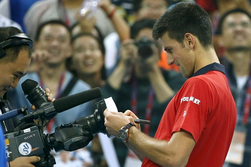 """Djokovic writes the Chinese character """"Fu"""" (Luck) for a TV camera after winning against Simone Bolelli."""