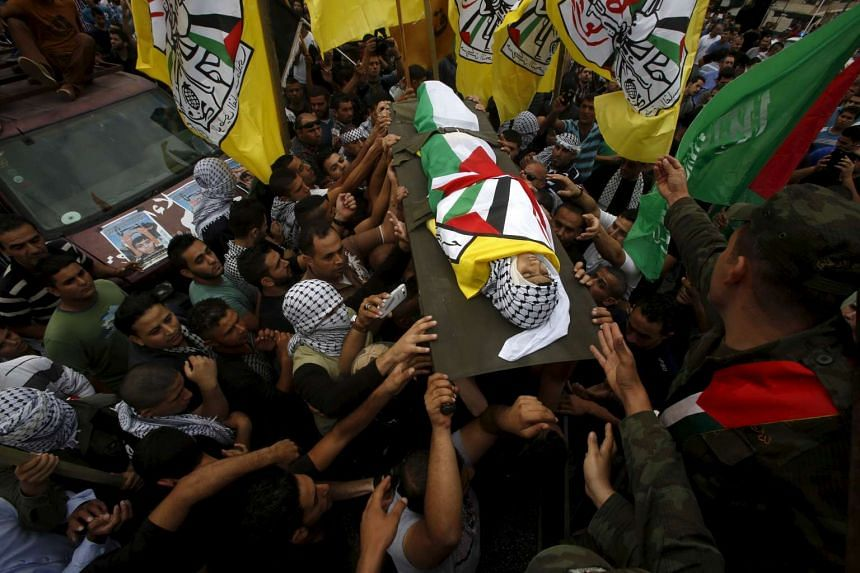 Mourners carry the body of 13-year-old Palestinian boy Abdel-Rahman Abeidallah, who was shot by Israeli troops during clashes on Monday, during his funeral in the occupied West Bank city of Bethlehem on Tuesday.