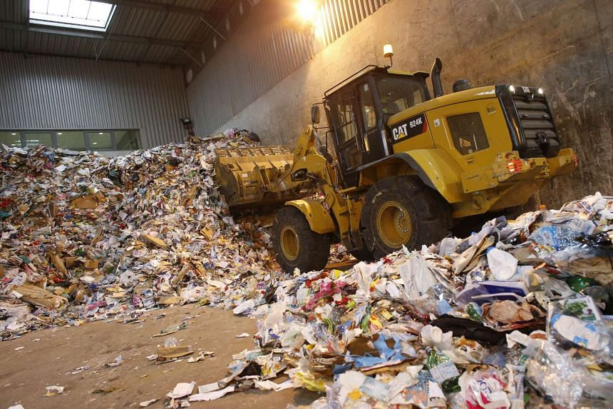 : A bulldozer moves trash for recycling at a sorting centre near Paris in advance of the upcoming United Nations' (UN) COP21 international climate conference.