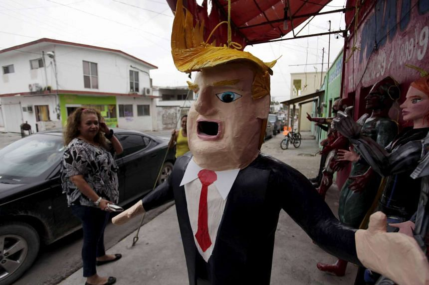 A Mexican client looks at a pinata depicting US Republican presidential candidate Donald Trump hanging outside a workshop in Reynosa, Mexico, in a June 23 photo.