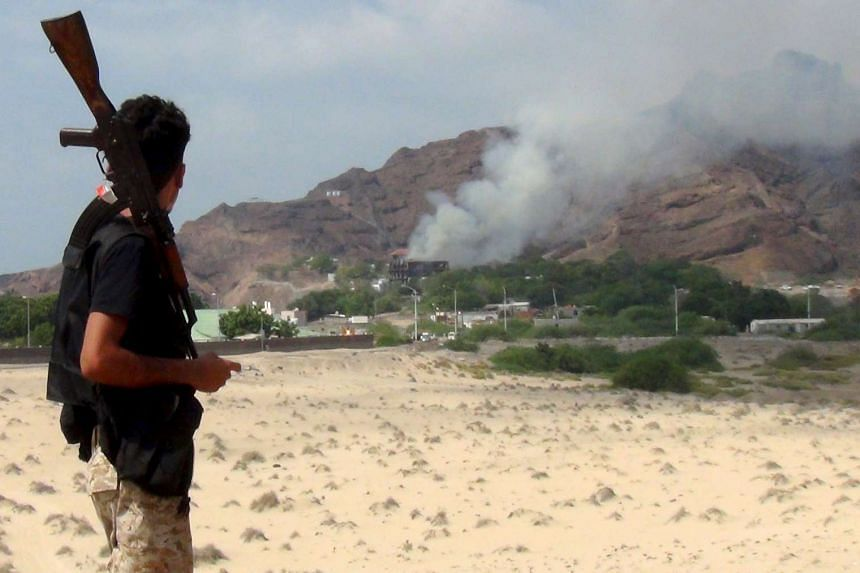 A militant loyal to Yemen's government looks as smoke billows from al-Qasr hotel after it was hit by explosions in the western suburbs of Yemen's southern port city of Aden on Tuesday.