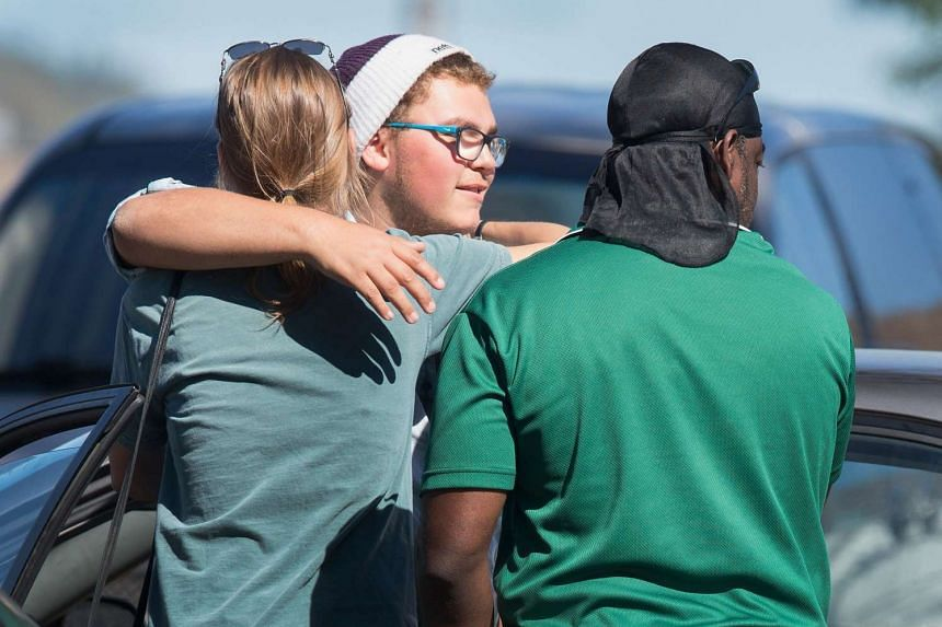Umpqua Community College shooting survivor Mathew Downing (centre) is greeted as he arrives on campus on Oct 5.