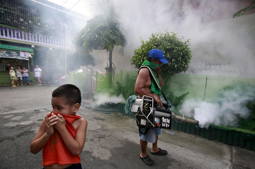 A boy covers his nose while a worker fumigates outside a residential area in Paranaque city, metro Manila, on Sept 26, 2015.