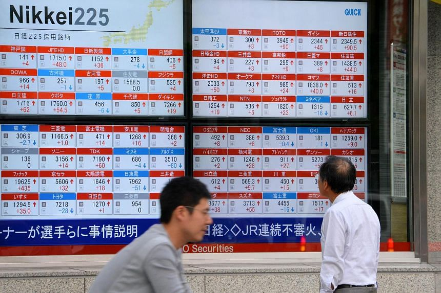 A man looks at an electronic board showing movement of the Nikkei 225 at the Tokyo Stock Exchange in Tokyo on Oct 6, 2015.