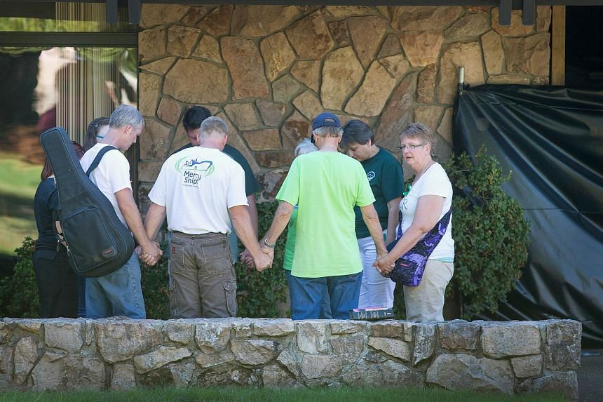 People hold a prayer circle outside Snyder Hall on the campus of Umpqua Community College on Oct 5, 2015 in Roseburg, Oregon.