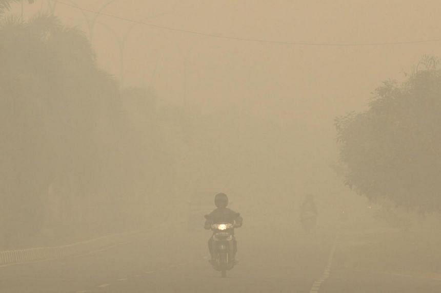 Motorists travelling under a thick haze in Palembang, on Indonesia's Sumatra island, on Sept 30, 2015.