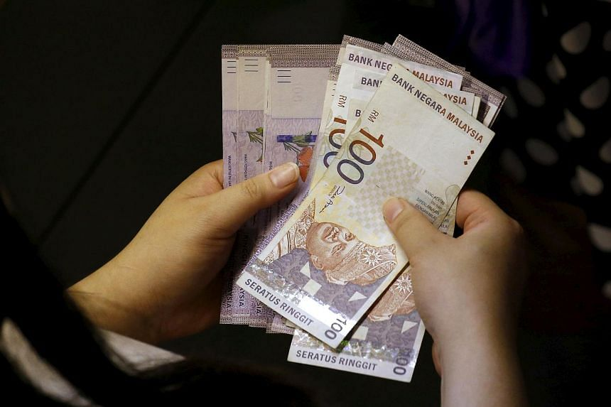 A customer counts her ringgit notes outside a money changer.