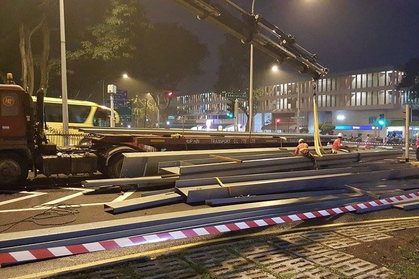 Workers preparing to retrieve metal i-beams that fell off a lorry on Marsiling Drive, at around 7.30pm on Oct 7, 2015.