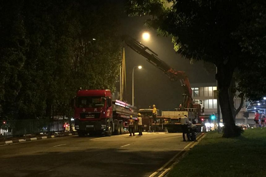 Workers using a crane to load the fallen i-beams onto the lorry at Marsiling Drive, on Oct 7, 2015.