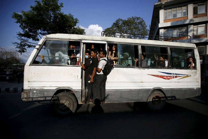 Passengers ride on an overcrowded bus as limited public transportation operates in the city during the ongoing fuel crisis in Kathmandu, Nepal.