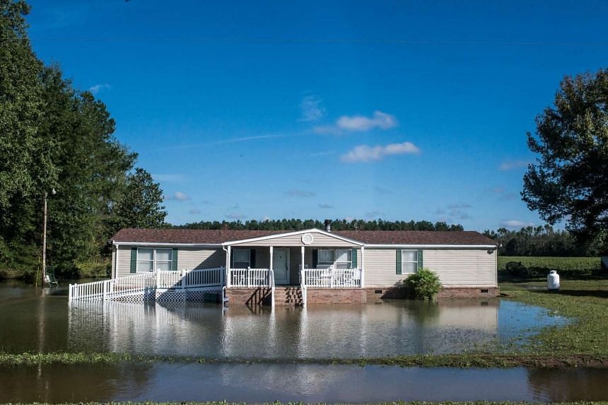 A house is surrounded by flood water after heavy rains on Oct 6, 2015 in Eastover, South Carolina.