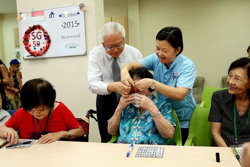 President Tony Tan Keng Yam helping a resident put on an N95 mask, during a visit to the St Andrew's Senior Care - JOY Connect in Kampong Glam on Oct 7, 2015.