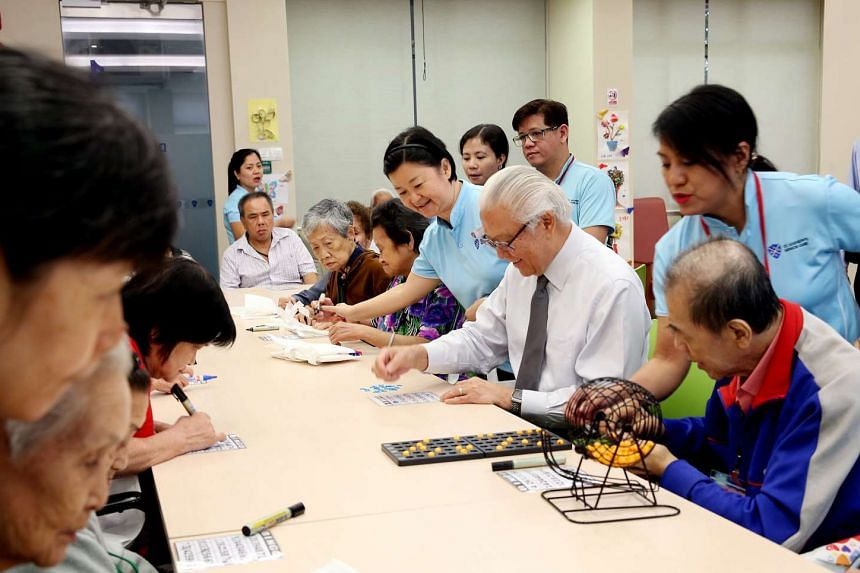 President Tony Tan Keng Yam playing a game of bingo with residents at St Andrew's Senior Care - JOY Connect in Kampong Glam, during a visit there on Oct 7, 2015.