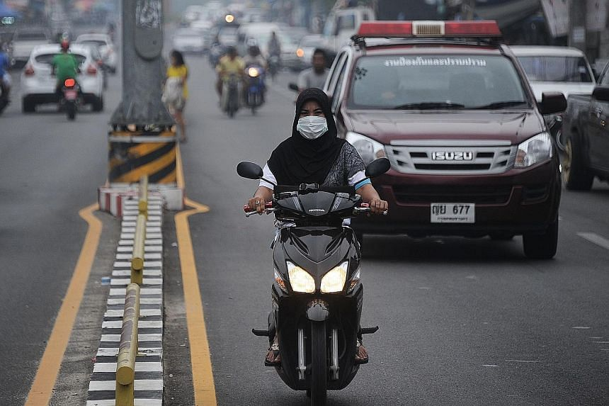 A motorcyclist, with face mask on, riding through haze-hit Narathiwat in southern Thailand on Monday. Thick haze blamed on forest fires in Indonesia has started to affect Thailand's southern provinces.