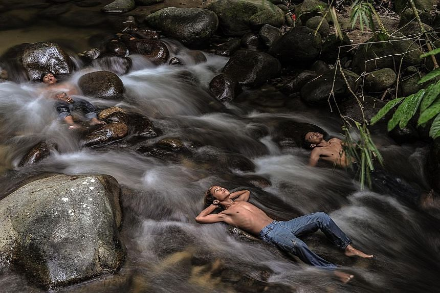 Young people in Malaysia getting some respite from the haze by cooling off in a river as schools remained closed due to hazy conditions in Hulu Langat, Selangor, yesterday. Forest and land fires raging in Sumatra and Kalimantan have intensified over