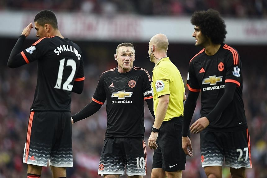 A flustered Manchester United skipper Wayne Rooney (centre) talking to referee Anthony Taylor. His team were ruthlessly exposed by Arsenal in the 3-0 defeat.