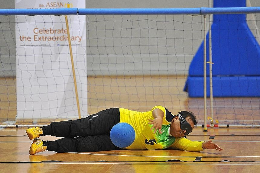 Above: Nazarudin, 37, goalball athlete, making a save. Left: Kamas Mohd and Chua Chong Hoi tussling in a wheelchair basketball demonstration event.