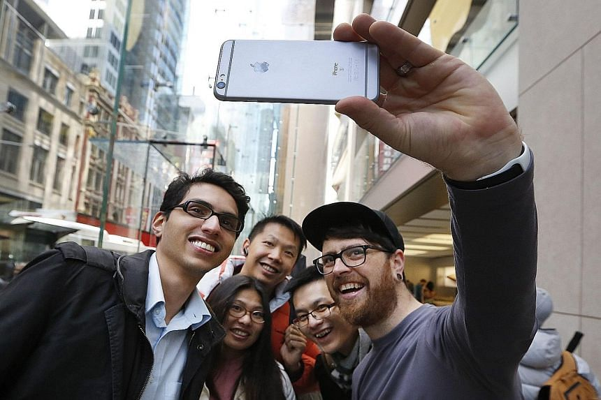 An Apple employee using an iPhone 6s to take a wefie with people queueing inside its Sydney store. Apple holds US$181.1 billion (S$258 billion) offshore, more than any other US firm, and would owe US$59.2 billion in US taxes if it tried to return the