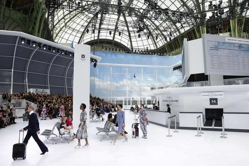 Models lining up to present creations by German designer Karl Lagerfeld for the airport-themed Chanel show in Paris.