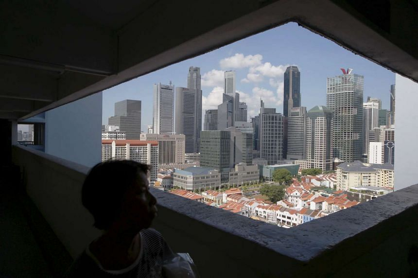 A woman passes the skyline of the central business district, in a public housing estate in Singapore.