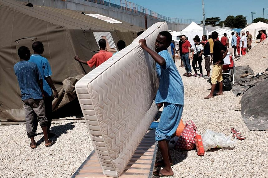 A migrant carries a mattress at a refugee camp next to the Tiburtina train station in Rome on Aug 20, 2015.