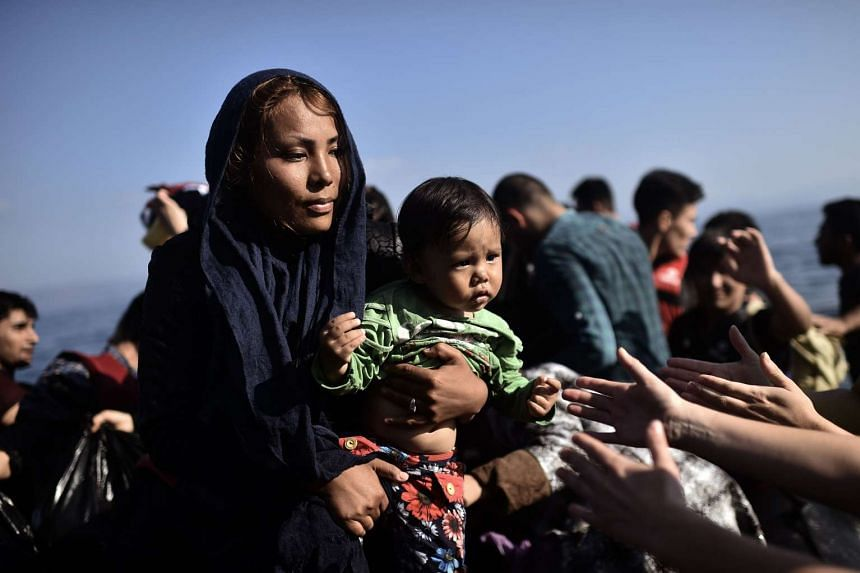 A migrant woman holding a child arrives at the Greek island of Lesbos after crossing the Aegean sea from Turkey on Oct 5.