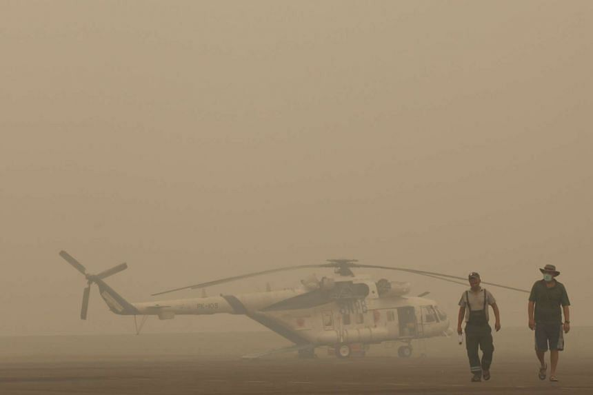 An Indonesian helicopter crew deployed for water bombing by the National Disaster Management Agency walking past their aircraft, which was grounded due to thick haze, in Palembang on Sept 30.