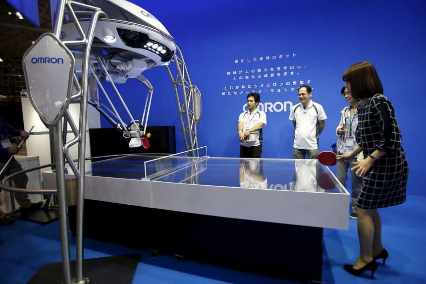 A woman plays table tennis with Japan's Omron Corp's table tennis playing robot at CEATEC (Combined Exhibition of Advanced Technologies) Japan 2015 in Makuhari, Japan, on Oct 6, 2015.
