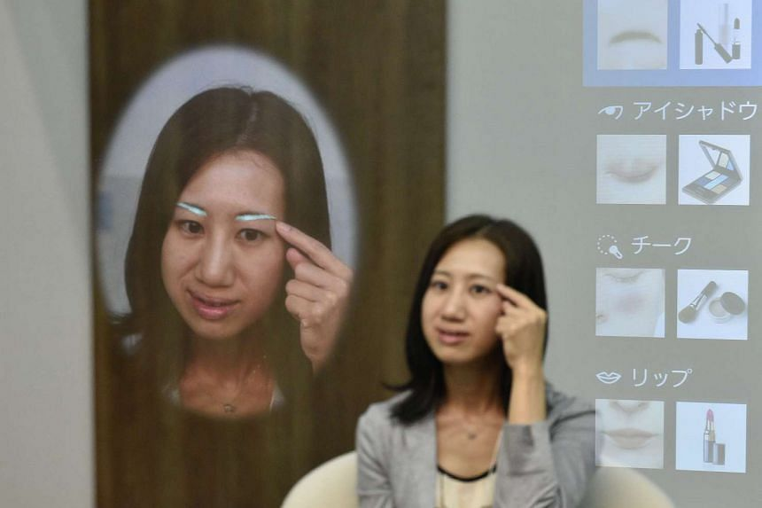 A young woman presents Panasonic's interactive mirror during the CEATEC (Combined Exhibition of Advanced Technologies) Japan 2015 exhibition at the Makuhari Messe in Chiba, east of Tokyo, Japan, on Oct 6, 2015.
