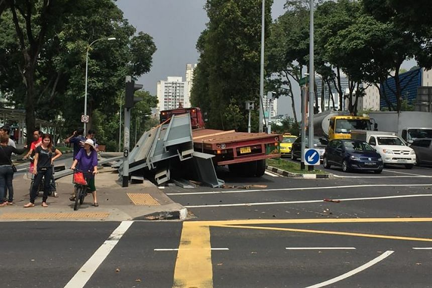The long vehicle, slightly listed to its left, with its cargo of heavy metal parts strewn all over Woodlands Centre Road at around 3pm on Oct 7, 2015.