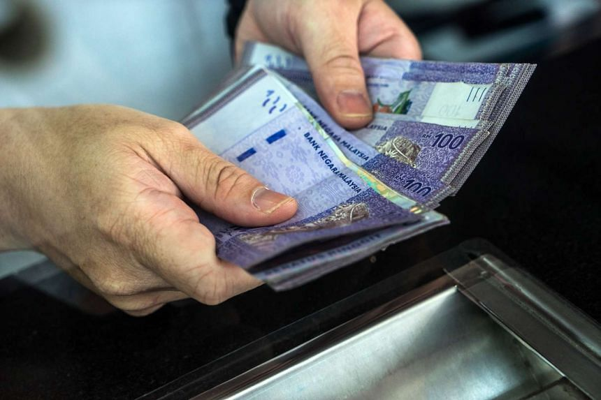 An employee counts Malaysian one-hundred ringgit banknotes at a currency exchange store in Bukit Bintang in Kuala Lumpur, Malaysia, on Aug 25, 2015.