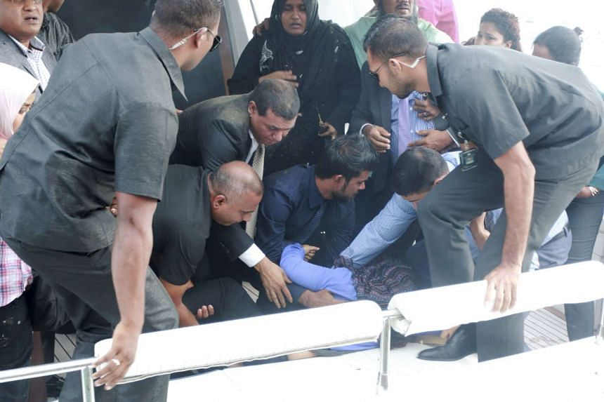 Officials carry an injured woman off the President's boat after an explosion onboard on Sept 28.