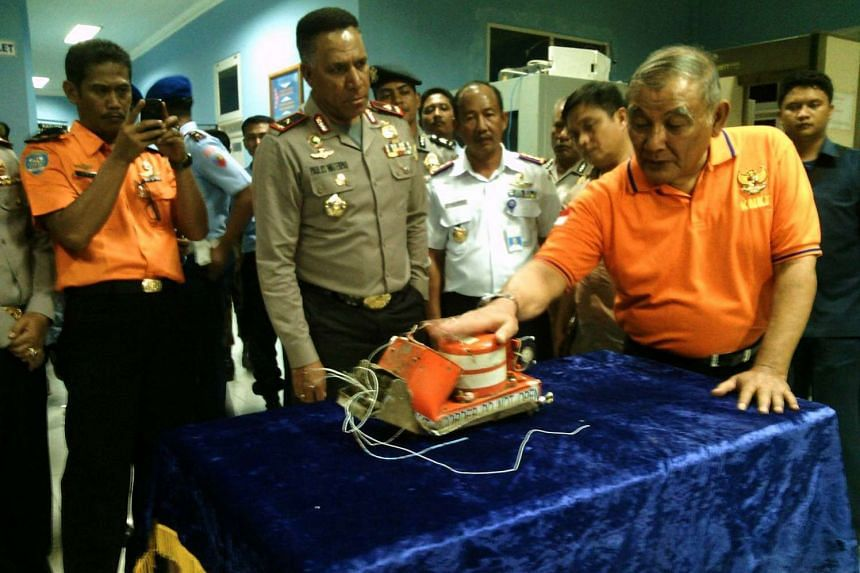 Indonesian police and transport safety officials display the recovered black box of Trigana Air Flight 267 in Jayapura after rescuers recovered the flight data recorders from the crash site near Oksibil, on Aug 17, 2015.