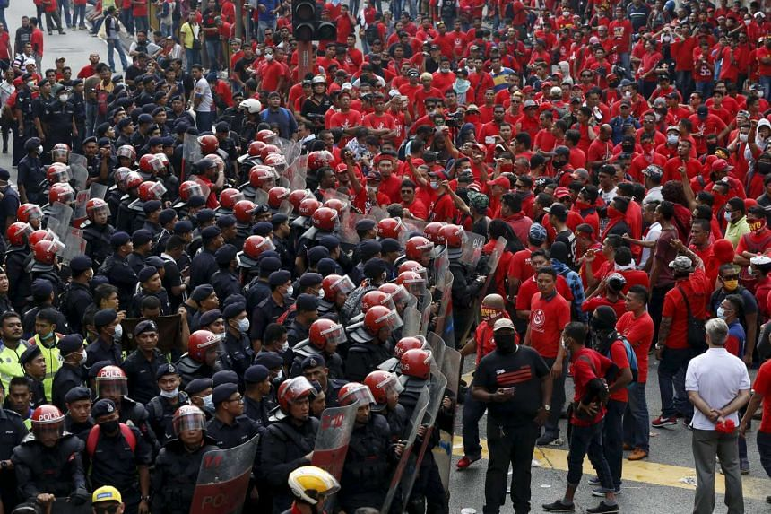 """Riot police protect the entrance to Chinatown from """"Red Shirt"""" demonstrators during a rally to celebrate Malaysia Day, on Sept 16, 2015."""