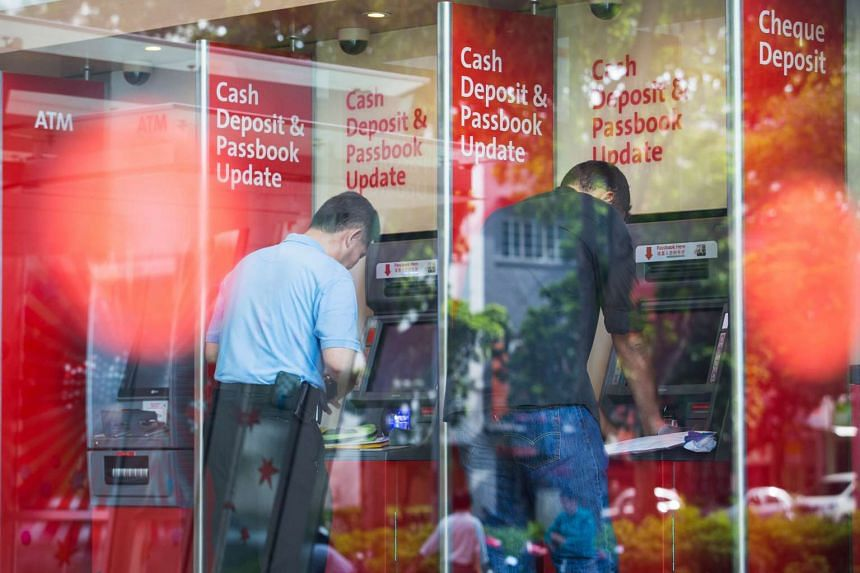 Customers using the cash deposit machines inside the OCBC bank branch at the OCBC Centre.