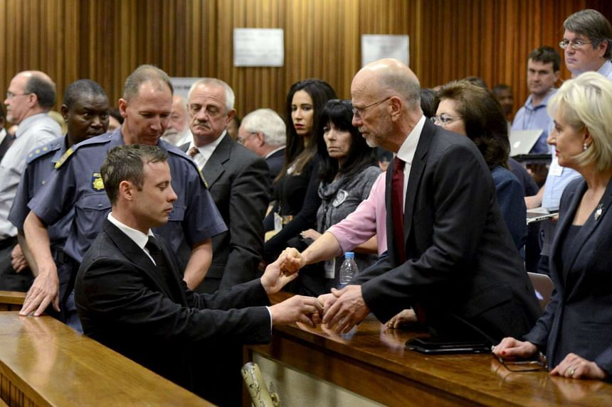 South African Olympic and Paralympic track star Oscar Pistorius (front left) holds the hands of family members after being sentenced at the North Gauteng High Court in Pretoria in this October 21, 2014 file photo.