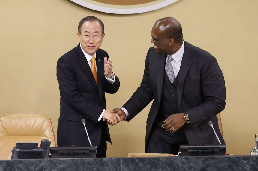 UN Secretary-General Ban Ki-moon greets United Nations General Assembly President John Ashe (right) of Antigua and Barbuda in a Sept 24, 2013 file photo.