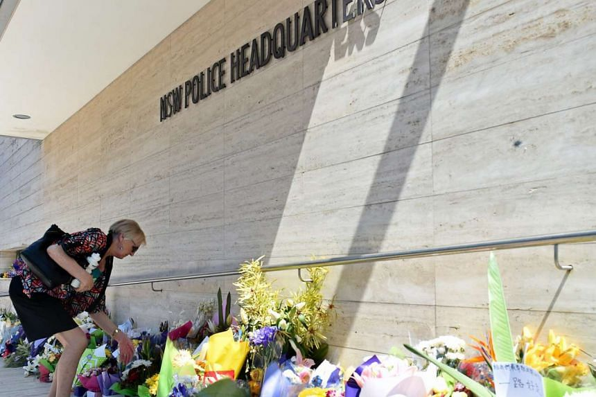 A women looks at flowers placed for police employee Curtis Cheng outside of the New South Wales Police Headquarters in Sydney, Australia, Oct 6, 2015.