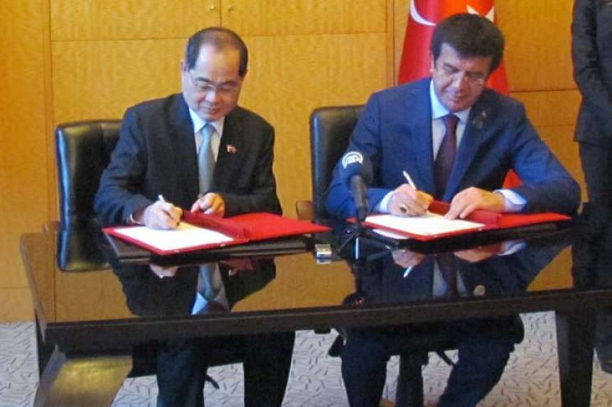 Trade and Industry Minister (Trade) Lim Hng Kiang and his Turkish counterpart, Mr Nihat Zeybekci, signing a joint statement in Istanbul.