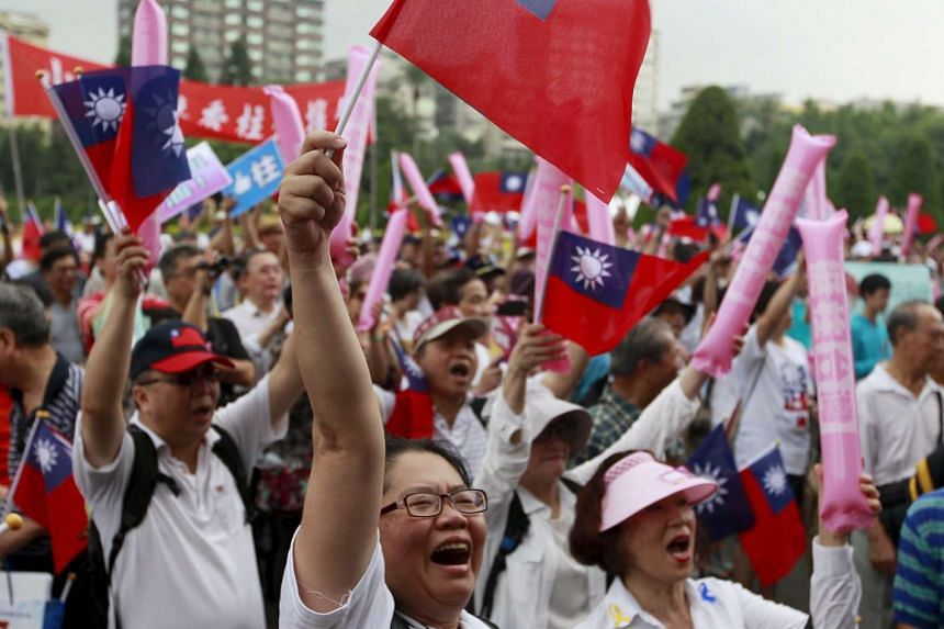 Supporters of Taiwan's ruling Nationalist Kuomintang Party (KMT) wave national flags during the party congress in Taipei, Taiwan, on Jul 19, 2015.