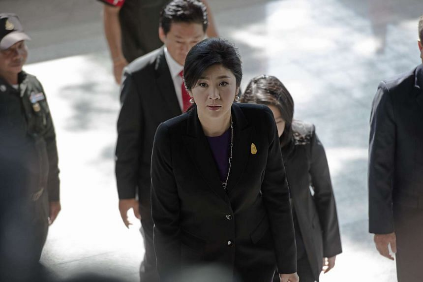 Ousted Thai prime minister Yingluck Shinawatra (center) arrives at a criminal court in Bangkok, Thailand, on Sept 29, 2015.