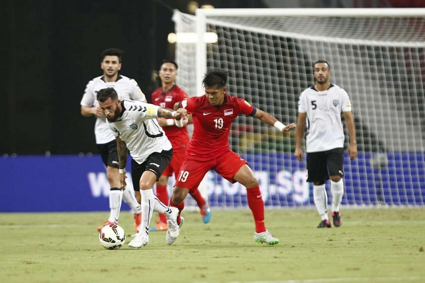 Khairul Amri tussling with Afghanistan's F Shayesteh during Singapore's 1-0 win at the National Stadium.