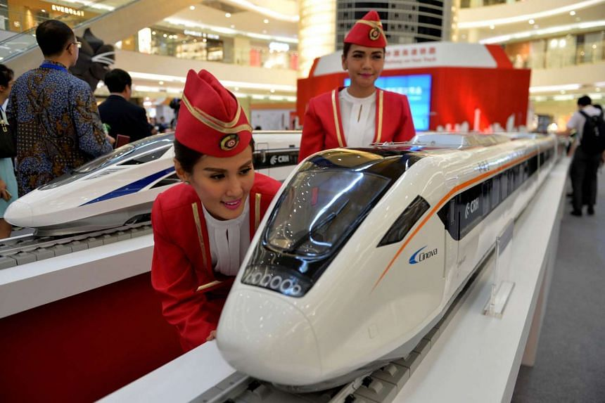 Indonesian models view scale models of Chinese-made bullet trains on exhibition at a shopping mall in Jakarta on Aug 13, 2015.