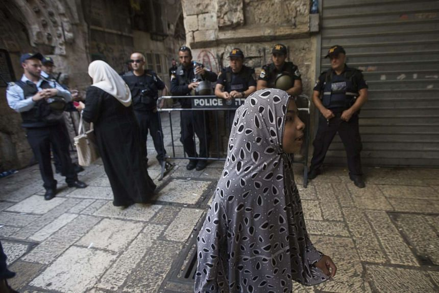 Palestinian women walk past Israeli police officers on duty in the old city of Jerusalem, on Oct 4, 2015.