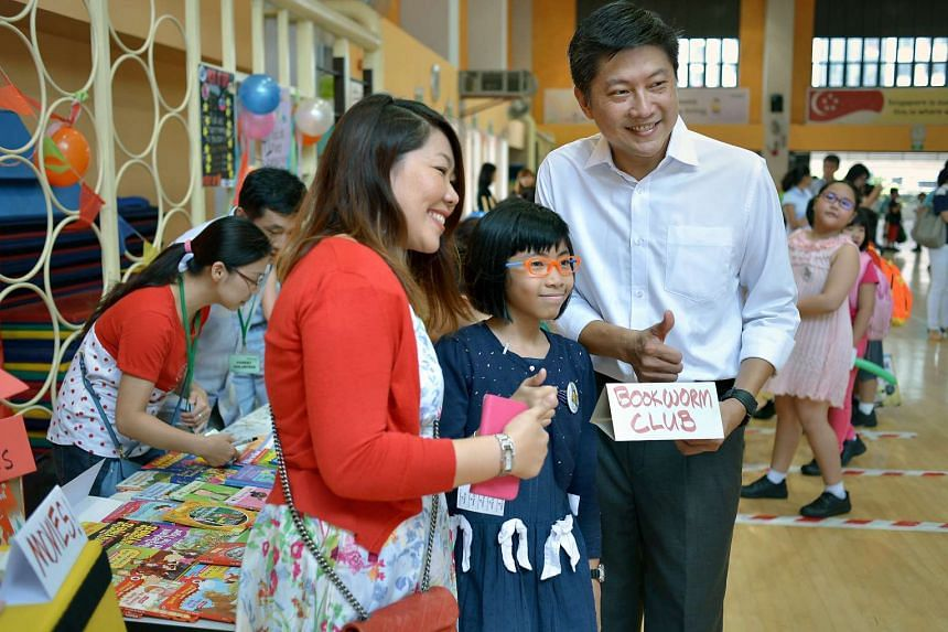Talia Astapura, 10, and her mother Julianah Johar posing for a picture with Acting Minister for Education Ng Chee Meng at the carnival at Frontier Primary School.