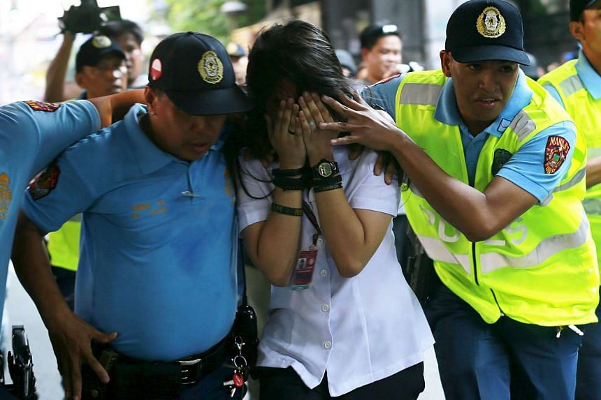 Philippine policemen assist a passenger to safety during a robbery incident inside a public bus in Manila on Oct 8, 2015.