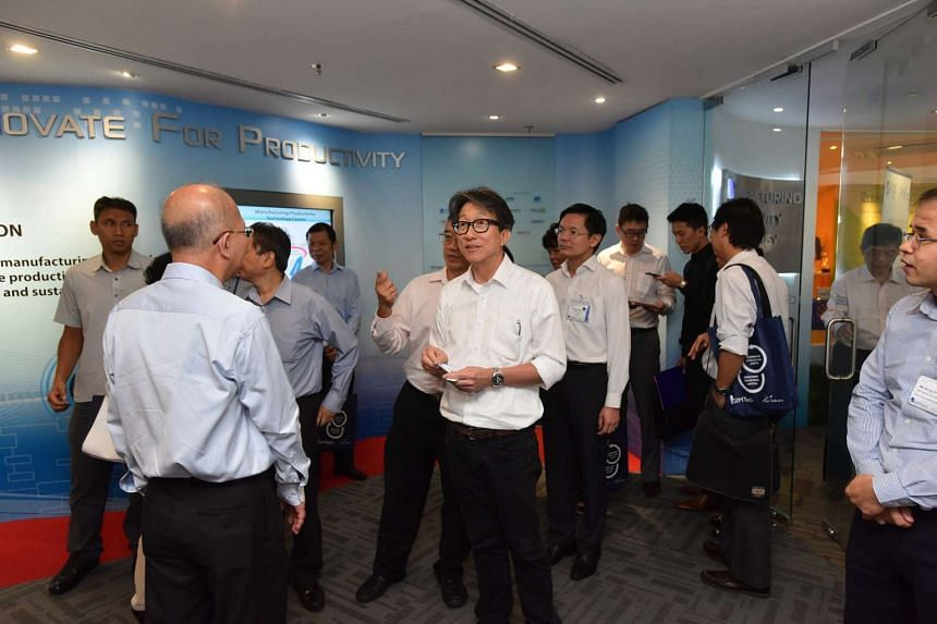 Manpower Minister Lim Swee Say talking with guests at a conference where the Singapore Institute of Manufacturing Technology signed a memorandum of understanding with Spring Singapore, on Oct 8, 2015.