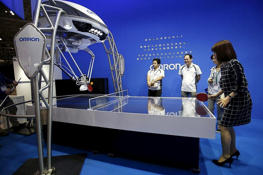 LEFT: A woman playing ping pong with a robot created by Japan's Omron. ABOVE: Sharp's Robohon, designed by robot creator Tomotaka Takahashi, can speak, dance and make phone calls.