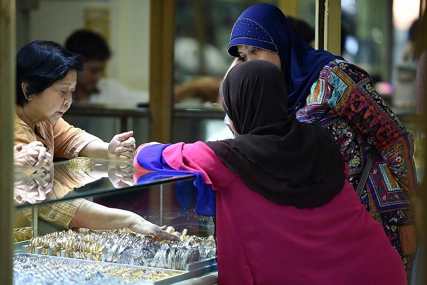 A gold jewellery vendor attending to customers in Jakarta. A softer US dollar helped lift gold to a seven-week high of US$1,148.65 an ounce, a spike of 3.8 per cent from $1,107.03 last Friday, and is up nearly 1 per cent from Tuesday.
