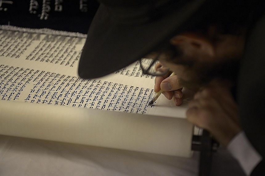 A new set of Torah - or Jewish written law - being completed at the Maghain Aboth Synagogue in Waterloo Street on Sept 30.
